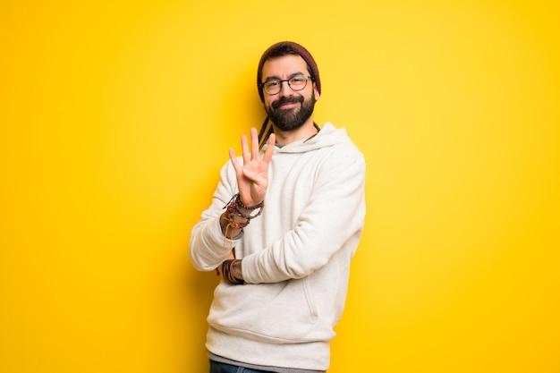 Hombre hippie con rastas feliz y contando cuatro con los dedos