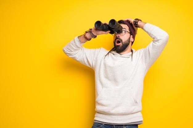 Hombre hippie con rastas y mirando en la distancia con binoculares