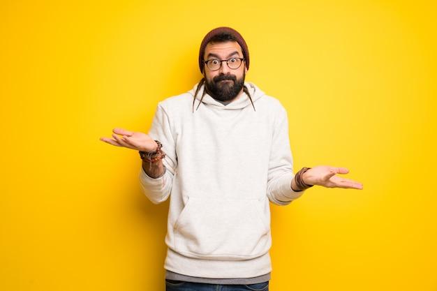 Hombre hippie con rastas que hace un gesto sin importancia mientras levanta los hombros.