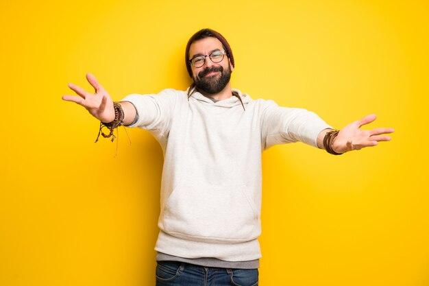 Hombre hippie con rastas que presenta e invita a venir con la mano.