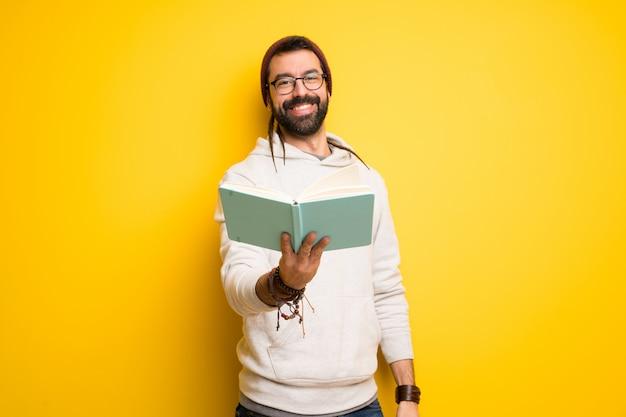 Hombre hippie con rastas que sostiene un libro y se lo da a alguien.