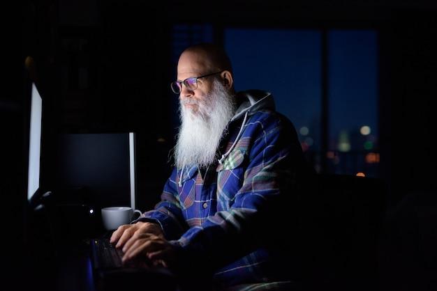 Hombre hipster barbudo calvo maduro con anteojos trabajando horas extras en casa por la noche
