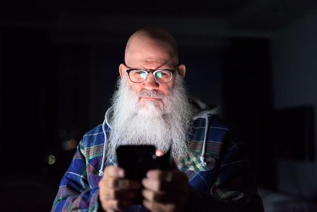 Hombre hipster barbudo calvo maduro con anteojos usando el teléfono en casa en la oscuridad