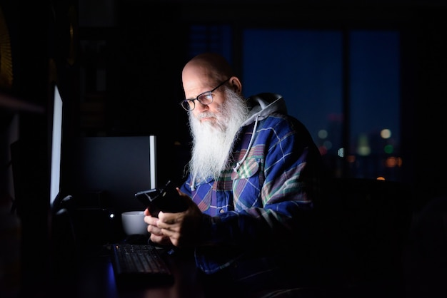 Hombre hipster barbudo calvo maduro con anteojos usando teléfono y trabajando horas extras en casa por la noche