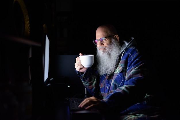 Hombre hipster barbudo calvo maduro feliz tomando café mientras trabaja horas extras en casa por la noche