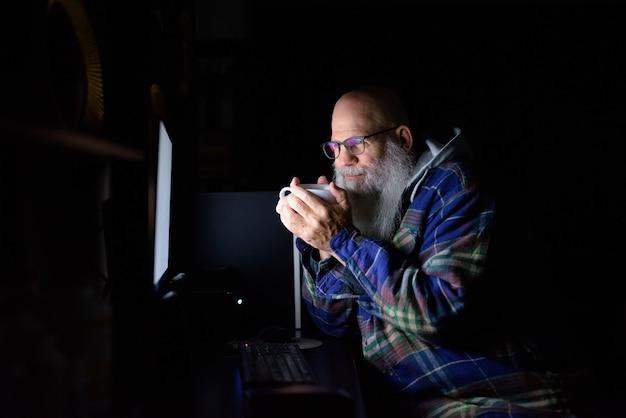 Hombre hipster barbudo calvo maduro tomando café mientras trabaja horas extras en casa por la noche