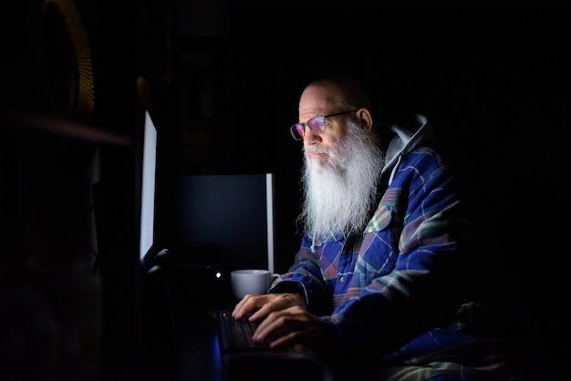 Hombre hipster barbudo calvo maduro trabajando horas extras en casa por la noche en la oscuridad