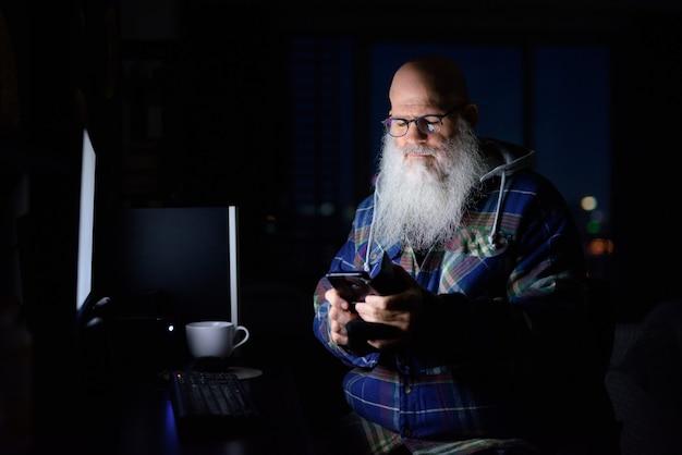 Hombre hipster barbudo calvo maduro usando el teléfono en casa a altas horas de la noche en la oscuridad