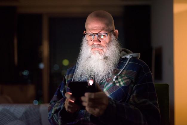 Hombre hipster barbudo calvo maduro usando el teléfono en casa en la oscuridad