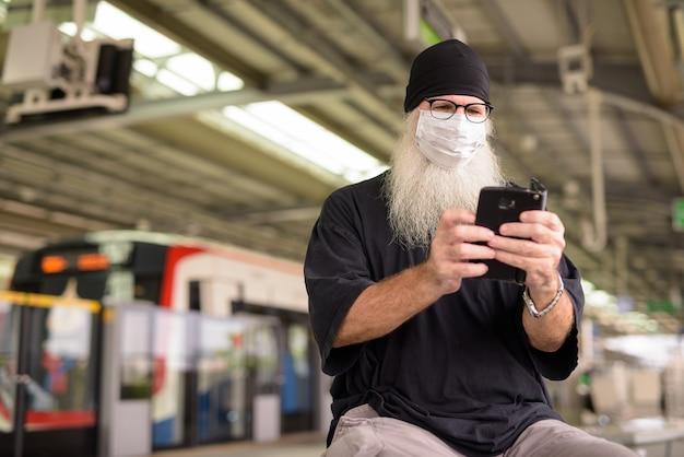 Hombre hipster barbudo maduro que usa el teléfono con máscara para protegerse del brote del virus corona en la estación de tren