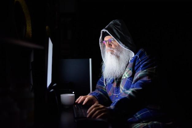 Hombre hipster barbudo maduro con sudadera con capucha trabajando horas extras en casa en la oscuridad