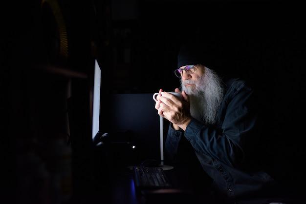 Hombre hipster barbudo maduro tomando café mientras trabaja horas extras en casa a altas horas de la noche en la oscuridad