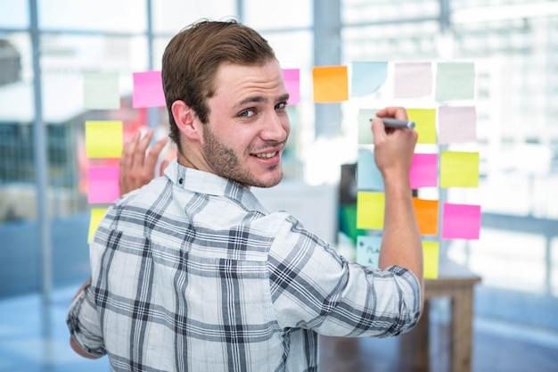 Hombre hipster escribiendo en post-it en la oficina