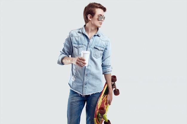 Hombre hipster en gafas de sol y chaqueta de jeans posando con patineta y café