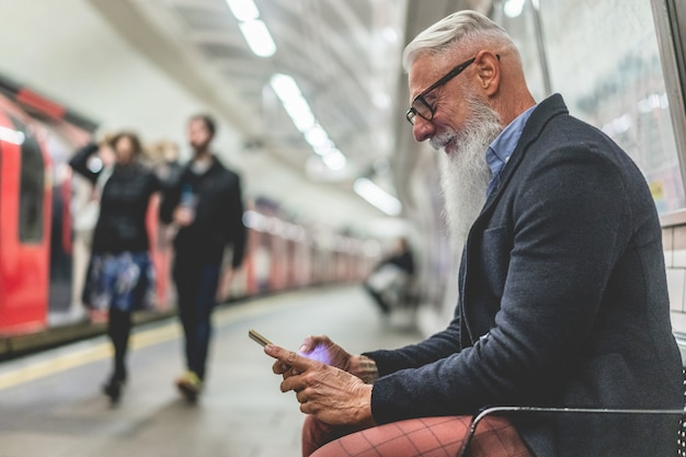 Hombre hipster senior con teléfono inteligente en el metro subterráneo - persona madura de moda divirtiéndose con tendencias tecnológicas esperando su tren - concepto alegre de estilo de vida de ancianos - enfoque principal en la mano de primer plano
