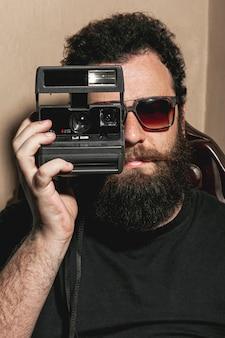 Hombre hipster usando una cámara de fotos vintage
