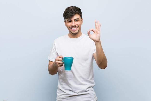 Hombre hispánico joven que sostiene una taza alegre y confidente que muestra gesto aceptable.