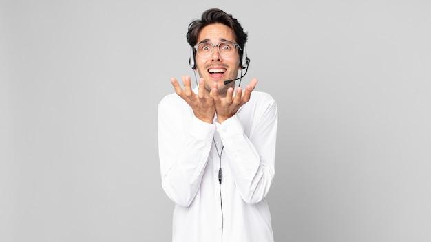 Hombre hispano joven que parece desesperado, frustrado y estresado. concepto de telemarketer
