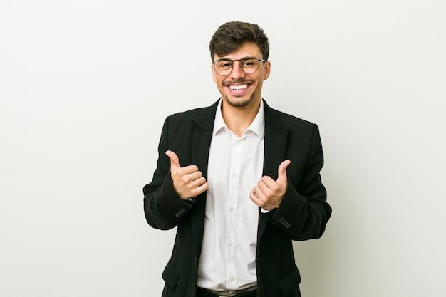 Hombre hispano de negocios jóvenes levantando ambos pulgares, sonriente y confiado.
