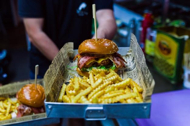 Hombre hispano sosteniendo una bandeja con una hamburguesa recién hecha y patatas fritas