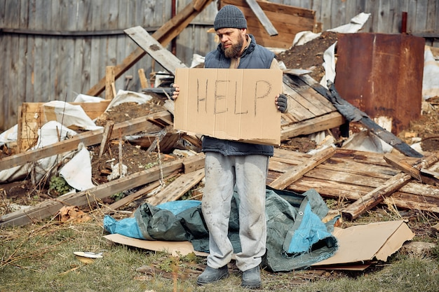 Un hombre sin hogar cerca de las ruinas con un cartel de ayuda, ayuda a las personas pobres y hambrientas durante la epidemia.