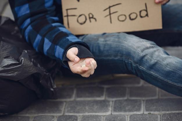 Hombre sin hogar en una ciudad durty ropa otoño