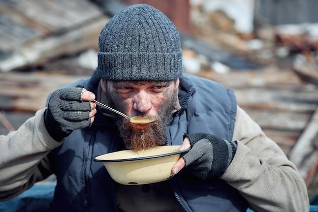 Un hombre sin hogar come sopa de un plato cerca de las ruinas, ayudando a las personas pobres y hambrientas durante la epidemia.