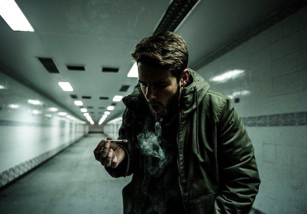 Hombre sin hogar fumando adicción al cigarrillo