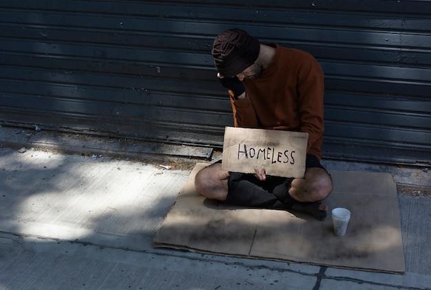 Hombre sin hogar ocultando su rostro y pidiendo dinero