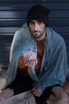 Hombre sin hogar pidiendo dinero alta vista