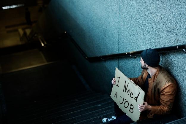Hombre sin hogar pidiendo trabajo sentado en la acera de la escalera