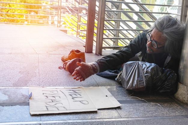 Un hombre sin hogar está sentado en la pasarela de la ciudad. él es la etiqueta de la muestra
