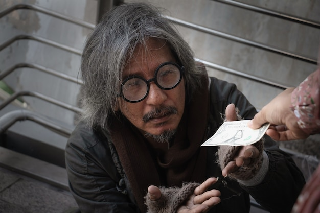 El hombre sin hogar se está sentando en la calzada en ciudad. él está sosteniendo el sombrero y recibe el dólar.