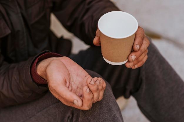 Hombre sin hogar sosteniendo la mano en busca de ayuda y taza vacía