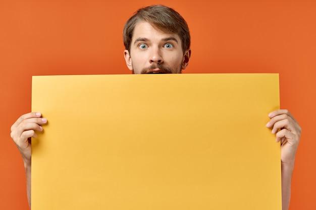Hombre con hoja naranja de papel maqueta de cartel marketing fondo aislado. foto de alta calidad
