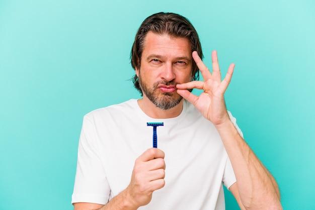 Hombre holandés de mediana edad sosteniendo una hoja de afeitar en azul con los dedos en los labios guardando un secreto.
