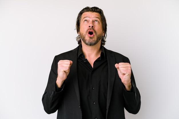 Hombre holandés de negocios de mediana edad aislado sobre fondo blanco apuntando al revés con la boca abierta.