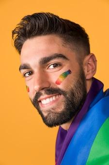 Hombre homosexual feliz cubierto por la bandera del arcoiris lgbt