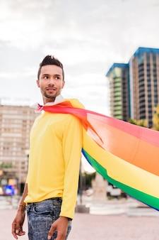 Hombre homosexual latino joven con la bandera del arco iris del desfile del orgullo gay estilo de vida capa de superhéroe