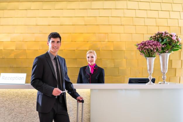 El hombre en el hotel se registra en la recepción o en la oficina de recepción recibiendo una tarjeta de acceso