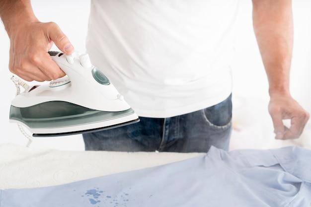 Hombre humeante ropa con plancha de ropa