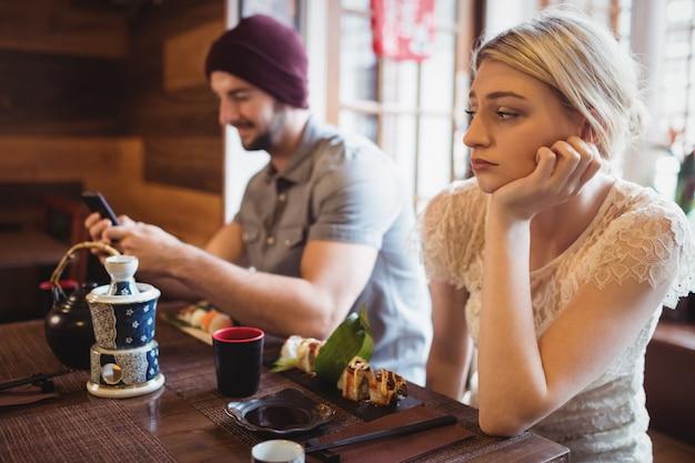 Hombre ignorando a la mujer mientras usa el teléfono móvil