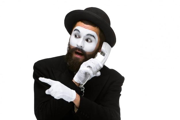 El hombre en la imagen imita sosteniendo un auricular.