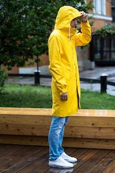 Hombre en un impermeable amarillo de pie sobre un piso de madera mojado