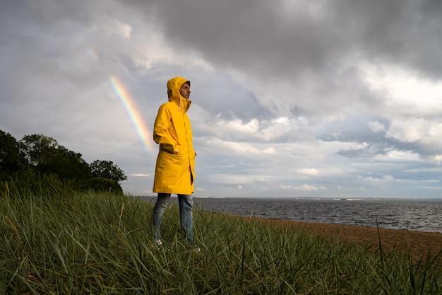 Hombre de impermeable con capucha camina en la playa en tiempo lluvioso y arco iris