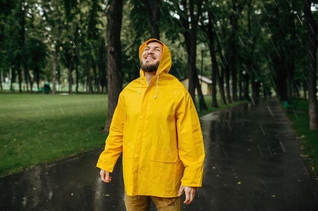 Hombre de impermeable disfrutando de la lluvia en el parque de verano. persona del sexo masculino feliz en la capa de lluvia en el sendero, clima húmedo en el callejón