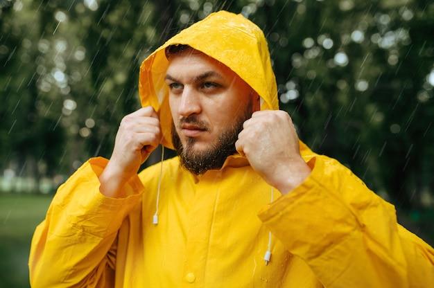 Hombre en impermeable se pone una capucha, parque de verano en día lluvioso. solo persona del sexo masculino en el cabo de lluvia en el sendero, clima húmedo en el callejón