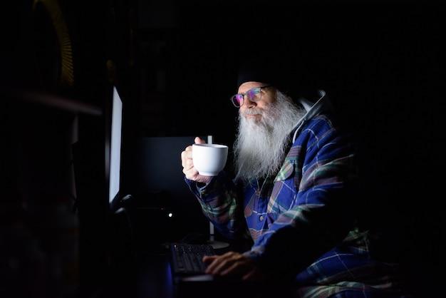 Hombre inconformista barbudo maduro feliz tomando café mientras trabaja horas extras en casa en la oscuridad