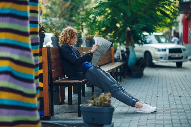 Hombre inconformista de pelo rojo acostado en el banco leyendo el periódico