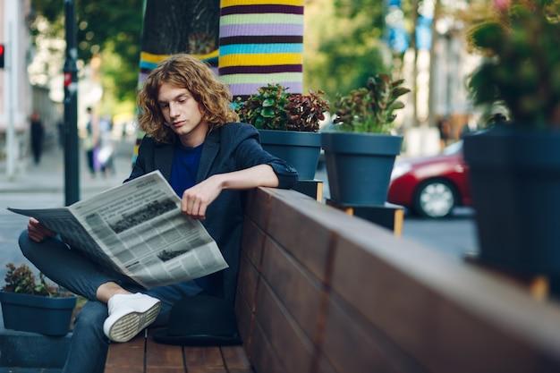 Hombre inconformista de pelo rojo sentado en un banco leyendo un periódico
